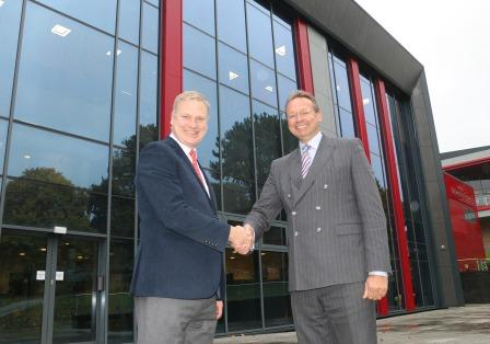Representatives from university and college shake hands to mark new partnership